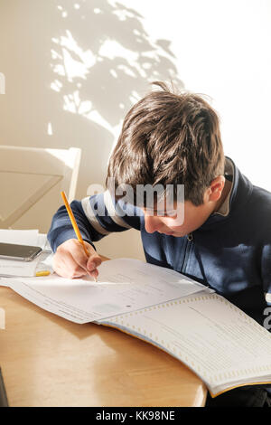 Schoolboy-10 years old,working on his homework,Surrey,UK - Stock Photo