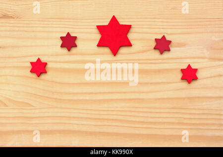 Christmas background, bow of red felt stars on wooden table - Stock Photo