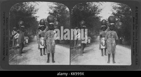 A photograph of three women standing on a road with earthenware jugs of water on their heads, they each have a cloth - Stock Photo