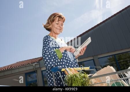 Senior woman using digital tablet with shopping cart | usage worldwide, Royalty free: For comercial usage price - Stock Photo