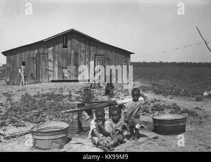 Black and white photograph of three African-American young children, two sitting, one standing, outdoors, a water - Stock Photo