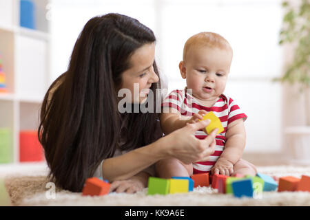 Mother with baby boy playing at home - Stock Photo