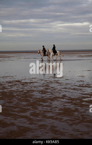 Two women horse riding on Holkham bay beach, Norfolk - Stock Photo