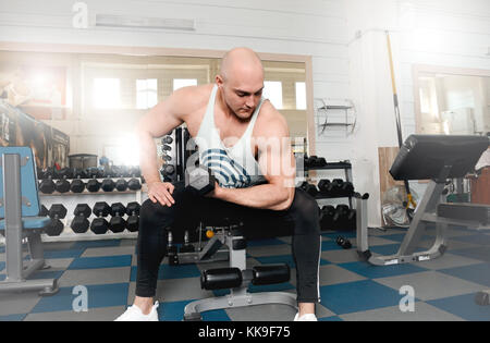 Very power athletic man bodybuilder do execute exercise with dumbbells on counter with dumbbells background. Fitness - Stock Photo