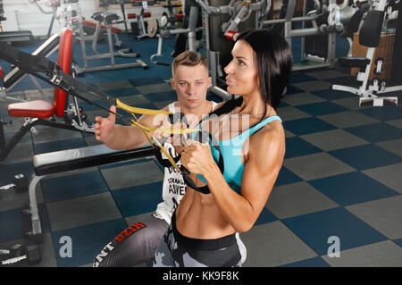Male trainer help young fitness woman execute exercise with exercise-machine. Instructor helping young woman training - Stock Photo