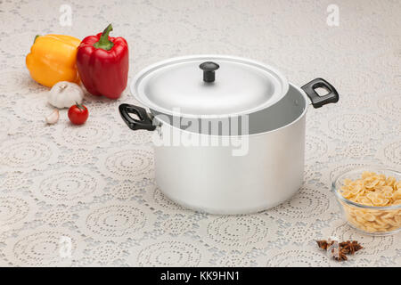 empty aluminum pan on the tablecloth with bell peppers and pasta in glass cup - Stock Photo