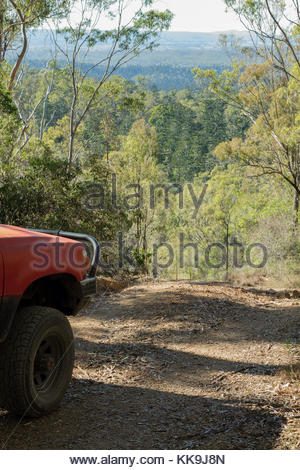 A dirt road leads a four wheel drive down a mountain in Goodnight Scrub National Park in Queensland, Australia. - Stock Photo