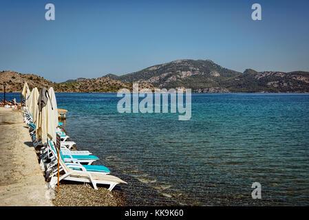 Sunbeds on a pebble beach in Selimiye, Agean sea, Marmaris, Turkey - Stock Photo