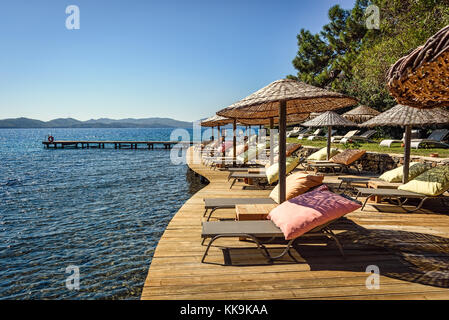 Sunbeds and sundshades on a wooden platform above the sea under clear blue skies, Agean sea, Marmaris, Turkey - Stock Photo