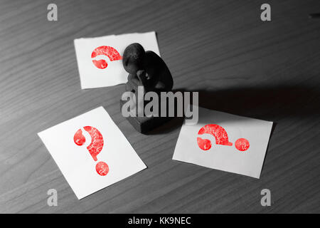 the thinker statue coil small on a desk with papers with copy space on the side and red queston marks black and - Stock Photo
