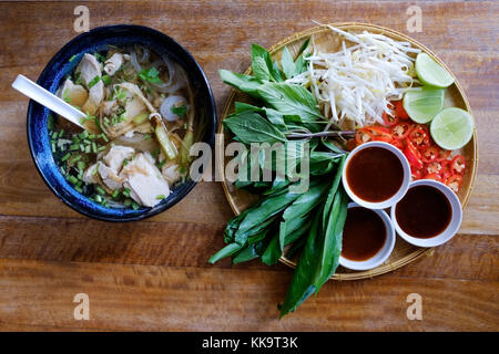 Traditional Vietnamese food. Soups, rolls and fresh herbs. Plates on a wooden surface. - Stock Photo