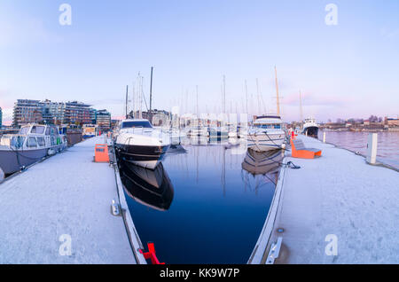 Mirror water inside frosty piers of Aker Brygge Marina in Oslo, Norway, at the beginning of the winter. - Stock Photo