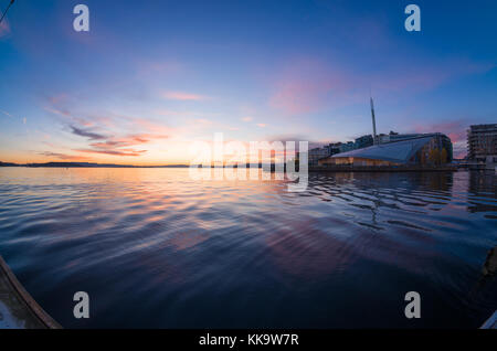 Waterfront of Tjuvholmen, Oslo, Norway, with Astrup Fearnley Museum, under colorful sunset, viewed from floating - Stock Photo