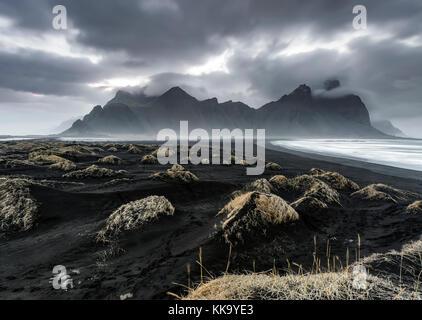 Looking across Icelandic black sand dunes towards the Vesturhorn Mountain - Stock Photo