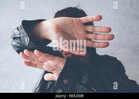 Celebrity male hiding face with hands from paparazzi photographers, no photos gesture - Stock Photo