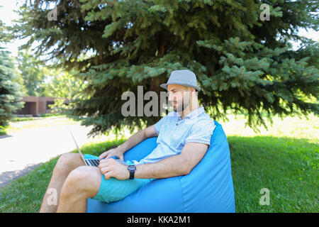 Jocund fun sitting in bag chair and supporting favorite sport sq - Stock Photo