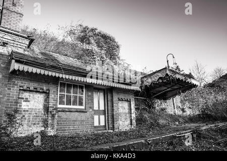 Black & white shot of disused Victorian station house in dilapidated state, in need of significant repair. Bricked - Stock Photo