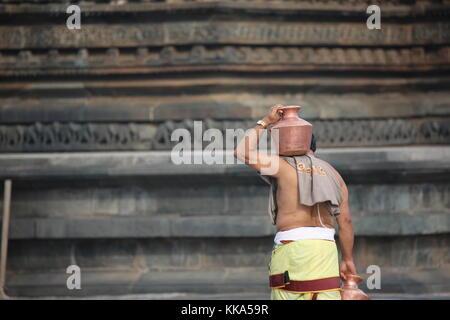 Morning in Chenna Keshava Vishnu Temple - priest with lota kalash pot making offerings - Priester mit Kuferkrug - Stock Photo