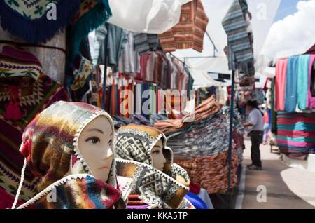 Otavalo market Ecuador, colourful textiles for sale in a market stall, Otavalo market, northern Ecuador, South America - Stock Photo