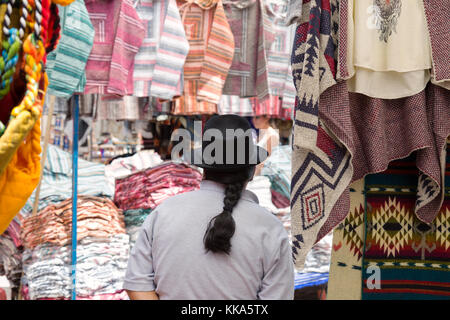 Indigenous man wearing hat and with ponytail as stall holder at a market stall, Otavalo Market, Ecuador South America - Stock Photo