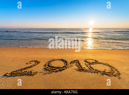 Number 2018 written on seashore sand at sunrise. Concept of upcoming new year and passing of time. - Stock Photo