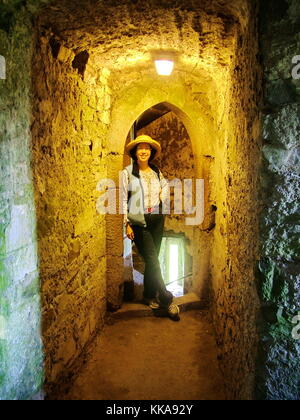 Tourist standing inside a stone hallway in Blarney Castle near Cork, Ireland - Stock Photo