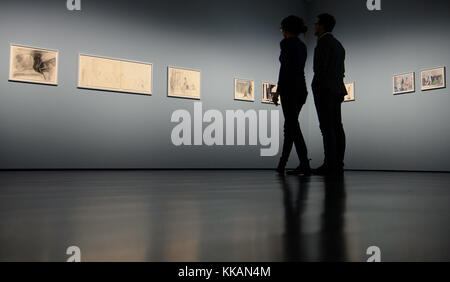 Two visitors stand in front of a row of paintings during a press preview of the exhibition 'Patrick Angus. Private - Stock Photo