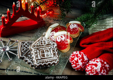 Two pie dough mittens and marmalade, with a gingerbread house on Christmas table. Copy space. - Stock Photo