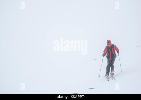 Ski touring in a snow blizzard white out at CairnGorm Mountain Ski Resort, Cairngorms National Park, Scotland, United - Stock Photo