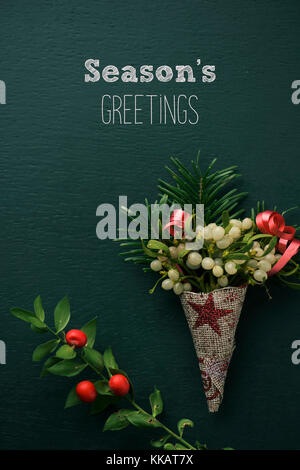 a bunch of mistletoe wrapped in a festive fabric, a twig of christmas holly and the text seasons greetings on a - Stock Photo
