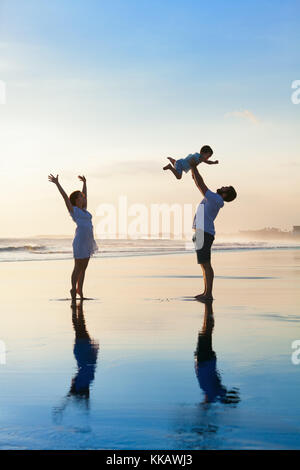 Father tossing high in air baby son, mother jumping by water pool. Happy family walk with fun by sunset black sand - Stock Photo