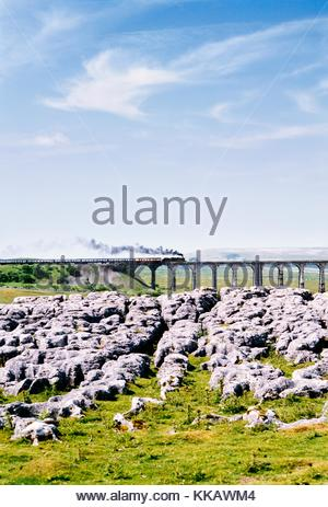 Steam railway engine train crosses the Ribblehead Viaduct in the limestone landscape of Yorkshire Dales National - Stock Photo