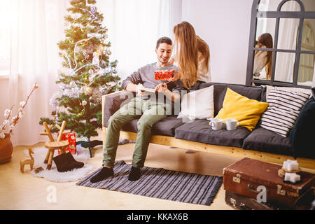 beautiful girl gives her boyfriend a present near christmas tree - Stock Photo