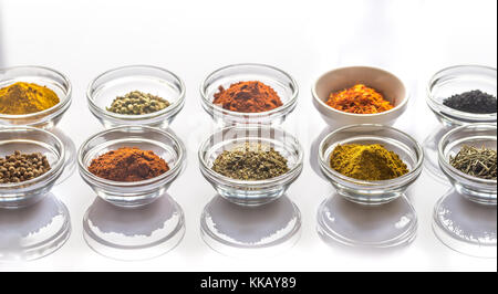Different kinds of spices and herbs on the white background - Stock Photo
