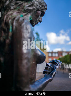 The Mermaid Fairy Tale Sculpture holding mask Odense Denmark - Stock Photo
