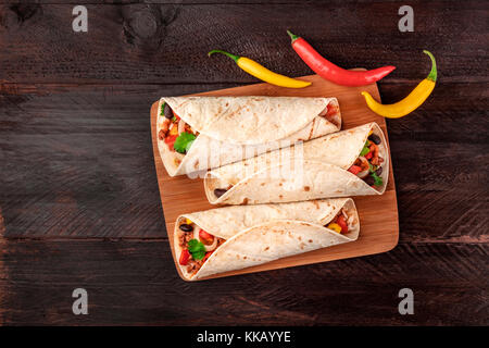 Mexican burritos with chili peppers, and copyspace - Stock Photo