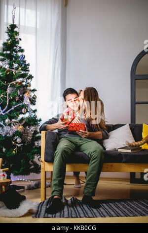 man opening a gift box while her girlfriend sitting close to her on couch - Stock Photo