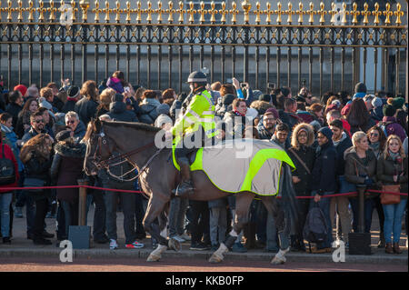 Metropolitan police woman on horseback at crowd control duty outside Buckingham Palace, London during Changing the - Stock Photo