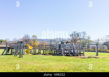 Wooden children's playground empty in countryside by school with slide in mountain countryside, rural - Stock Photo