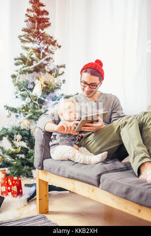 baby with father sitting and using digital tablet during Christmas - Stock Photo