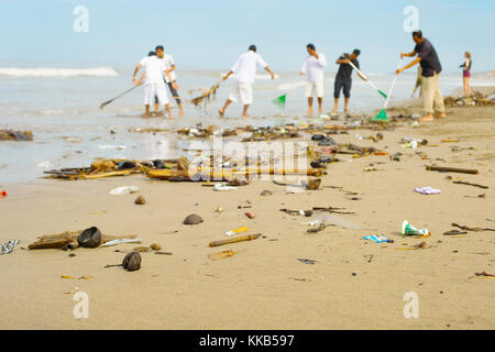 People cleaning trashy polluted with garbage ocean beach. Bali island, Indonesia - Stock Photo