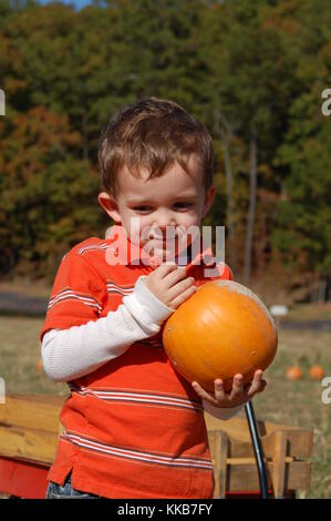 Young boy holding pumpkin in a pumpkin patch in North Little Rock, Arkansas and smiling as if he's daydreaming - Stock Photo