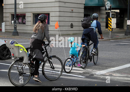 A young family with small child and baby riding bikes in a downtown street in the city of Portland, Oregon USA  - Stock Photo