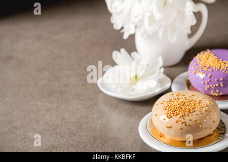 Fashionable mousse cake with a mirror glaze decorated with spring flowers. Dark background. - Stock Photo