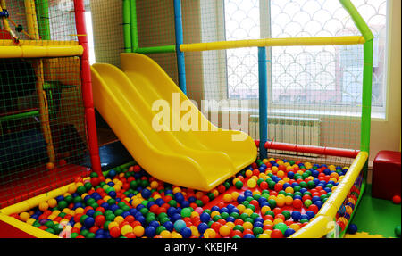 Yellow baby slide going down to the  pool with many colored balls in the kids playing room. - Stock Photo