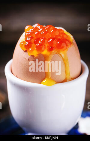Breakfast with soft-boiled egg with red caviar in white eggcup, served over blue ceramic plate. See series - Stock Photo