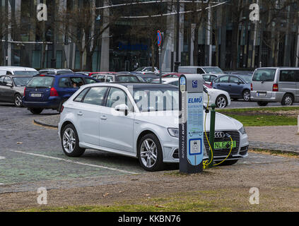 Charging modern electric Audi E-Tron car on the off-street parking from electric vehicle charging station. Eco-car - Stock Photo