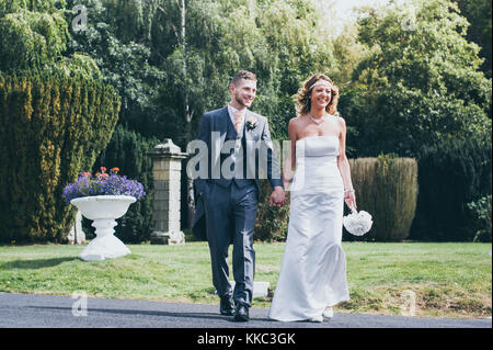 Newlywed couple holding hands and walking outdoors - Stock Photo