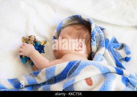 Cute newborn baby sleeping in blue blanket with figure of angel in hands on white background. - Stock Photo