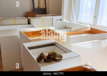 Installing new induction hob in modern kitchen Installation of kitchen cabinet. - Stock Photo